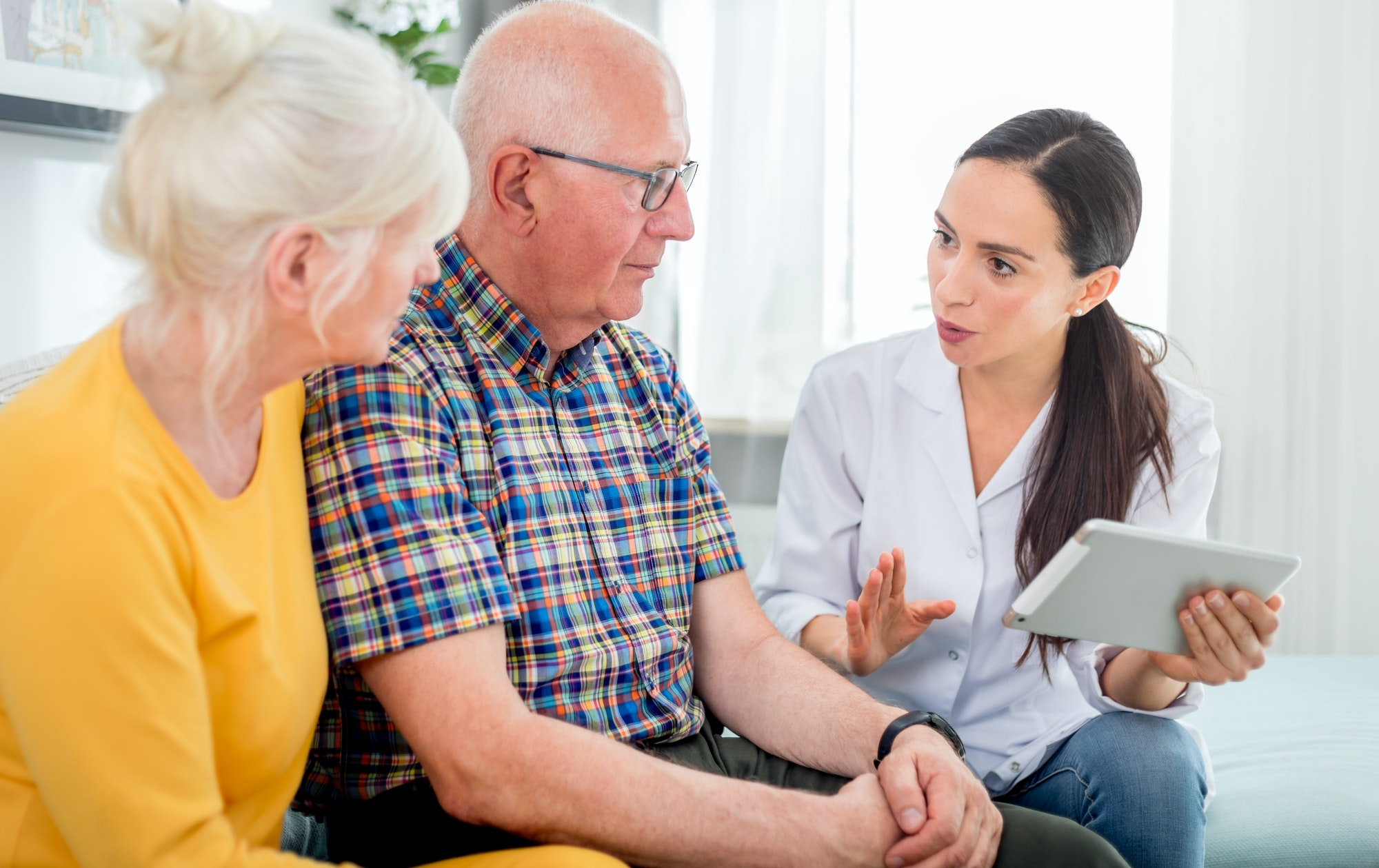 Nurse gives treatment advices to senior couple at home